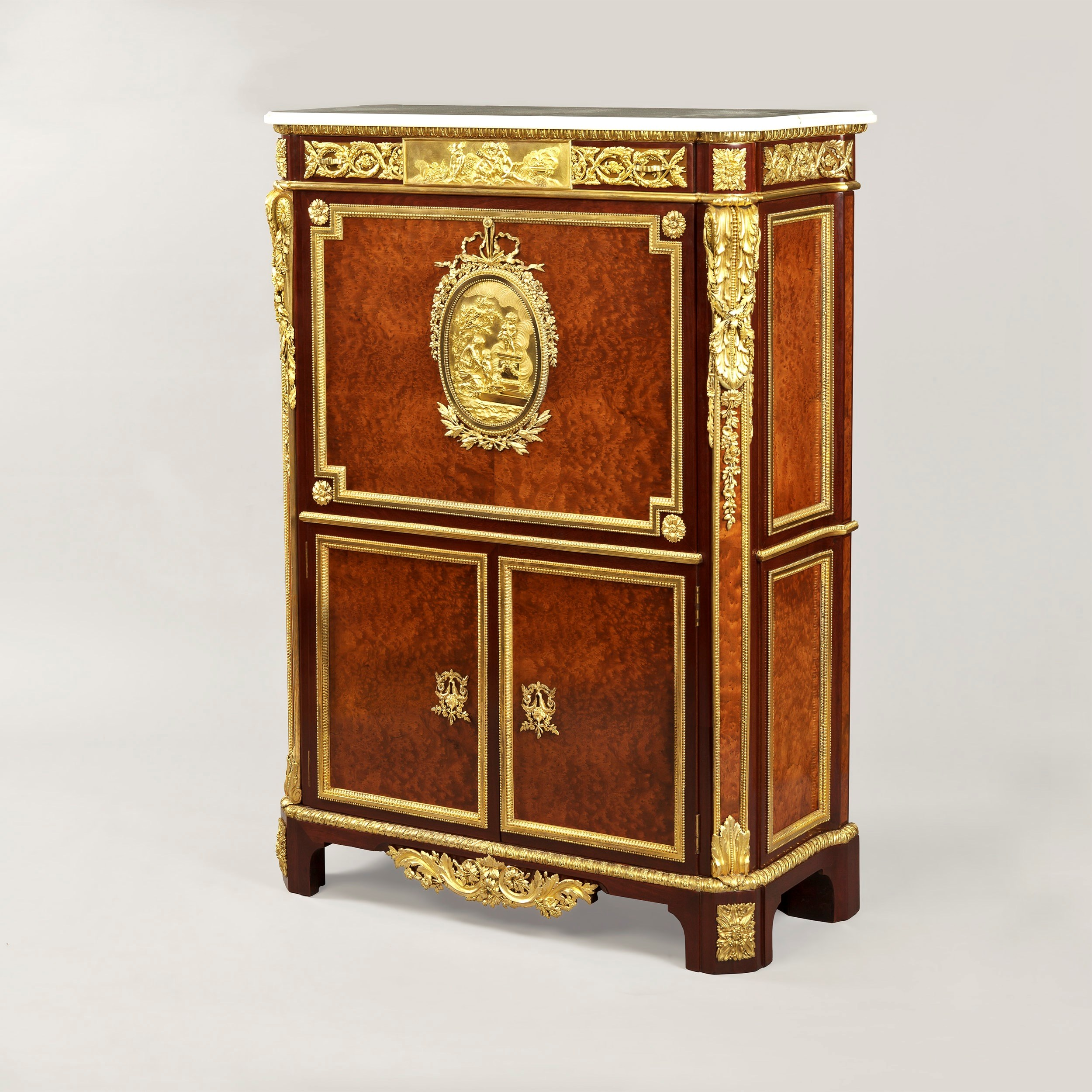 An Exceptionally Rare Secrétaire,  After the J.H. Riesener example in The Wallace Collection  Of upright rectangular form with canted corners; veneered in thuya-wood, and banded in purple-wood, exuberantly dressed with gilt bronze mounts of the highest quality, and having a Carrara marble top. Rising from bracket feet, the lower apron has a strong gilt bronze mount of stiff leaf acanthus foliates and volutes; the lower section has two lockable doors, with laurel wreathed escutcheons, the recessed panels, with gilt bronze frames, enclosing a shelf fitted interior. Over, the counter weighted lockable fall front has conforming recessed panels, mounted with a stepped gilt bronze indented band, the corners with rosettes of bay leaves, interspersed with berries. At the centre, an elliptical gilt bronze panel, depicting 'A Sacrifice to Love', a classically dressed woman presenting an infant to Cupid, who stands on a pedestal, wreathed by the scent from a brazier. The plaque has ribbon tied flowers, including roses, myrtle, narcissi and lilies-of-the-valley above, and below. The fall front encloses an interior fitted with drawers and pigeonholes.  The top frieze houses a drawer, having a centrally posited rectangular plaque, depicting three infants, one playing with a spaniel, one holding an open book, and handing a letter to the third infant, who wears the winged cap of Mercury, and has his caduceus at hand. The plaque issues sprays of roses, pinks, carnations and other flowers, with rosaces at the angles.  Over, a gilt bronze egg and dart band frames the shaped Carrara top. The canted front angles are pilasters, mounted with gilt bronze spandrels, cast as stiff leafed acanthus, having attached sprigs of oak leaves, berries and intertwined forget-me-nots, all within a gilt bronze stepped band.  Below, smaller acanthus leaf spandrels are dressed with chased volutes.   The sides are recessed and housed within running gilt bronze bands as seen on the lower doors, with a guard