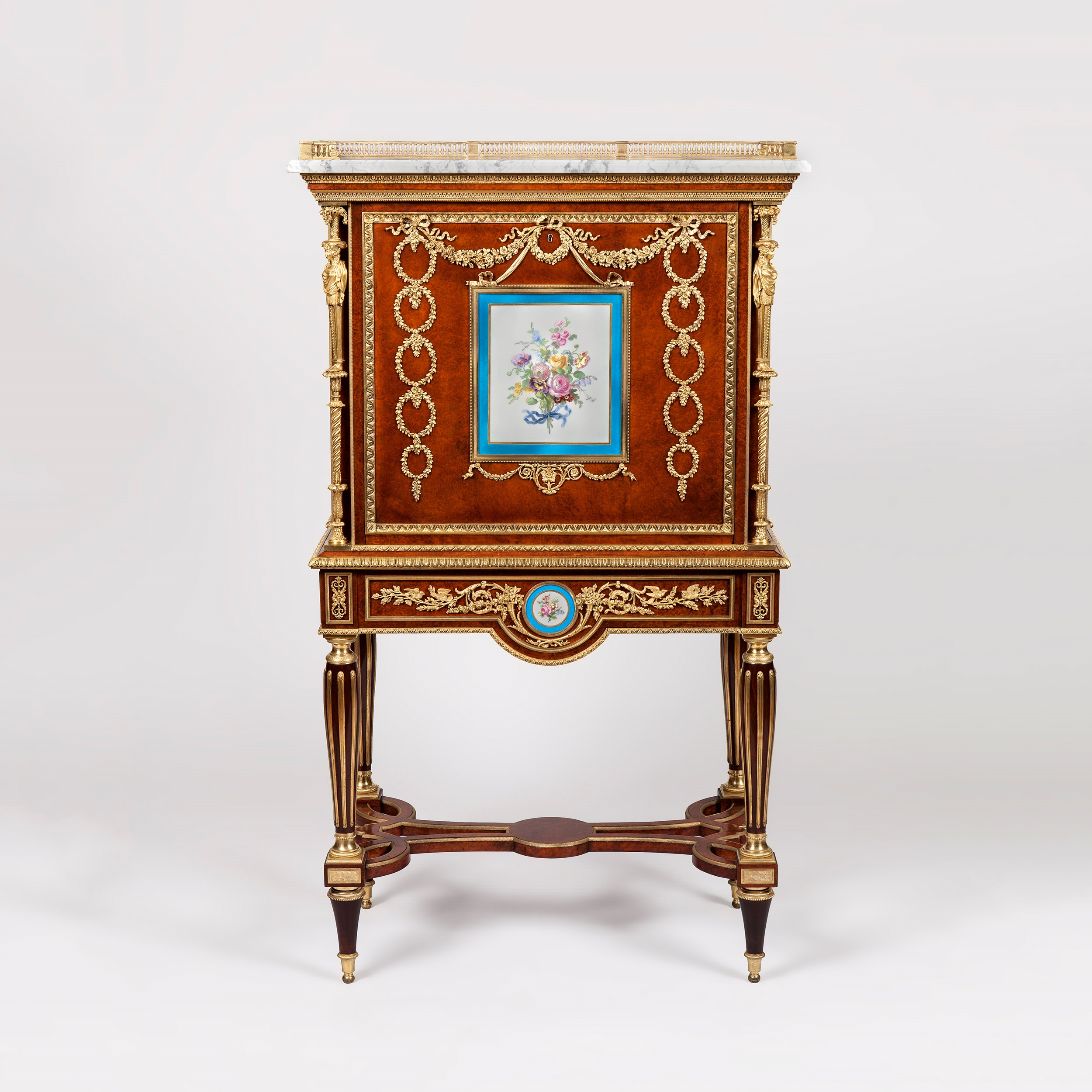 A Fine Escritoire After a Design by Adam Weisweiler  Constructed in amboyna, dressed with 'Sevres' porcelain plaques and gilt bronze mounts; rising from tapering circular legs, inlaid with brass, having bronze bases and capitols, and conjoined with an interlaced stretcher; the shaped apron, having a circular porcelain plaque and bronze foliates, houses a single cedar lined drawer, spring released by a concealed button; over, the secretaire, the drop flap fitted with a French lock, has a square bronze framed Sevres plaque, hand painted with roses within a  'bleu celeste' and gilt reserve, and extensive entrelac foliates, opens to reveal a fiddle back satinwood interior, fitted with an arrangement of three upper short drawers, and a lower single drawer, fitted with ring pulls; gilt bronze caryatids, in the form of festooned Grecian maids bearing baskets of flowers flank the fall-front, and the panelled sides are set with stiff leaf gilt bronze castings, and over, a thumb nail moulded white marble top is dressed with a three quarter arcaded bronze gallery. France, Circa 1870  Dimensions: H: 54 in / 137 cm  |  W: 32 in / 81 cm  |  D: 17 in / 43 cm  Provenance Christie Manson & Wood sale of pieces from the late Edward Huntley Walker and Edward Wertheimer collection, 1932, lot 43   The Metropolitan Museum of Art has in its collection a similar secrétaire à abattant attributed to Weisweiler, circa 1787 (accession no. 58.75.57). It is presumed that this was piece was originally located at Versailles and owned by Marie-Antoinette. After the angry mobs stormed Versailles in 1789, the royal family lived under house arrest in the Chateau des Tuileries. During this time the queen consigned her treasured possessions for safekeeping. An inventory of 1794 indicating royal seized furniture records a 'secretary with drop front, mounted with a large Sèvres plaque and ten medallions forming garlands.'   Our escritoire is of similar form to the model in the Metropolitan Museum of Art, p