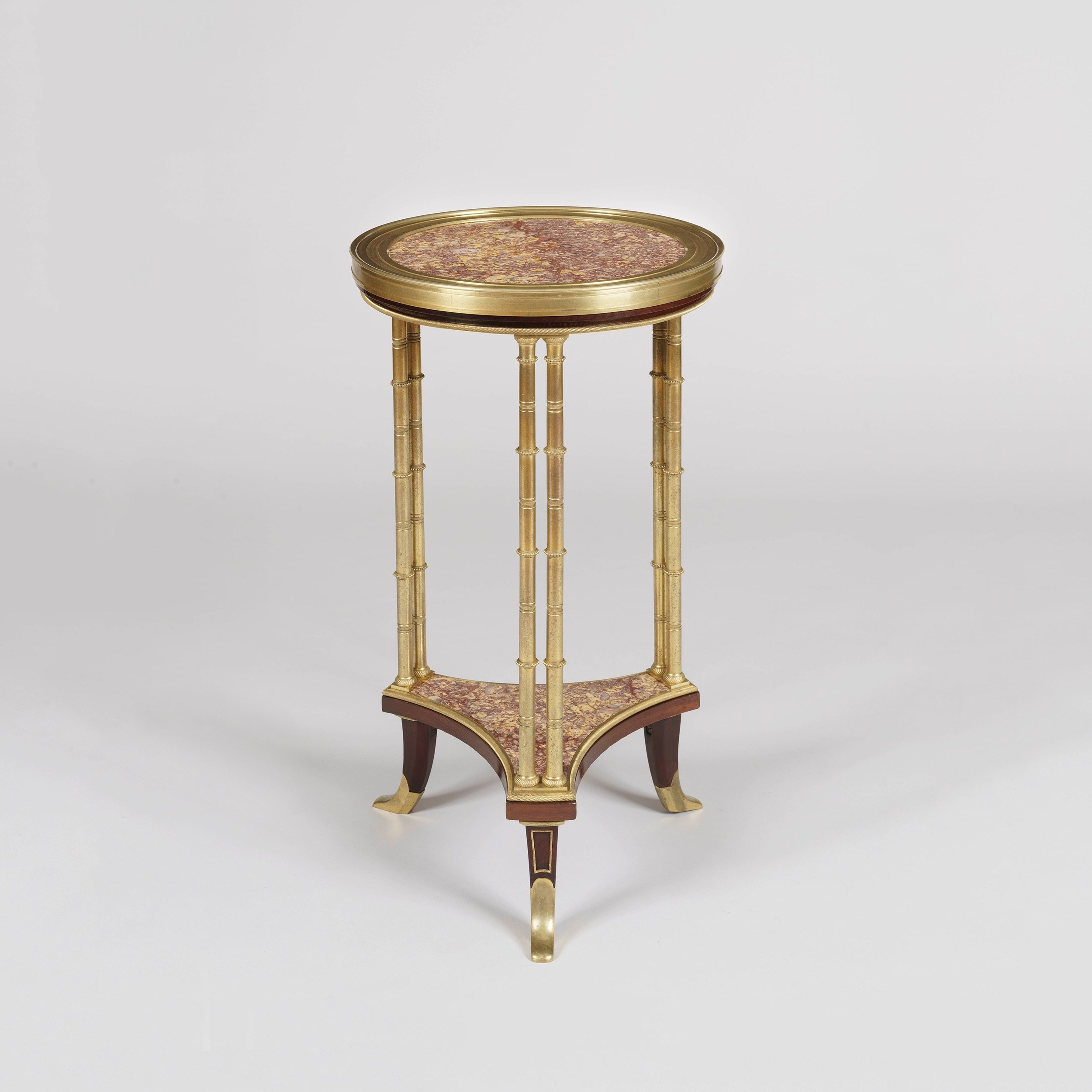 """A Fine Guéridon in the Manner of Adam Weisweiler by Henry Dasson Constructed in Brocatelle d'Espagne marble and mahogany, with finely cast and chased gilt bronze mounts; the top tier of circular form supported on cluster legs of bamboo shape in the typical manner of Weisweiler. The columns joined by a concave-shaped lower tier supported by flared feet dressed with gilt bronze sabots. This celebrated model of gueridon exemplifies the height of taste at the end of the eighteenth century, it was given by Madame du Barry (1743-1793) to the duc de Brissac, delivered by Lignereux and Daguerre. Daguerre's inventory describes a table of corresponding description """"Une petite table ronde forme de guéridon en racine de bois d'acajou poli sur trois pieds doubles en bronze doré façon de bambous avec entrejambe à tablettes et camé de porcelaine ornant la tablette supérieure prisée trois cent francs."""" (Segoura, Maurice, and Patricia Lemonnier. Weisweiler. Paris: Monelle Hayot, 1983.) Henry Dasson became renowned in the nineteenth century for his furniture based on historical designs, often incorporating stylistic elements created by Weisweiler (see Payne, Christopher. Paris Furniture: The Luxury Market of the 19th Century. [S.L.]: Editions D'art Monelle, 2018.). Christopher Payne maintains that """"His [Dasson's] best work must be the combinations of elements from Riesener and Weisweiler in a modernised Louis XVI manner"""" (p. 315) as seen in the present gueridon. Signed and dated 'Henry Dasson. 1878.' French, 1878 Dimensions: H: 26 in / 65 cm  