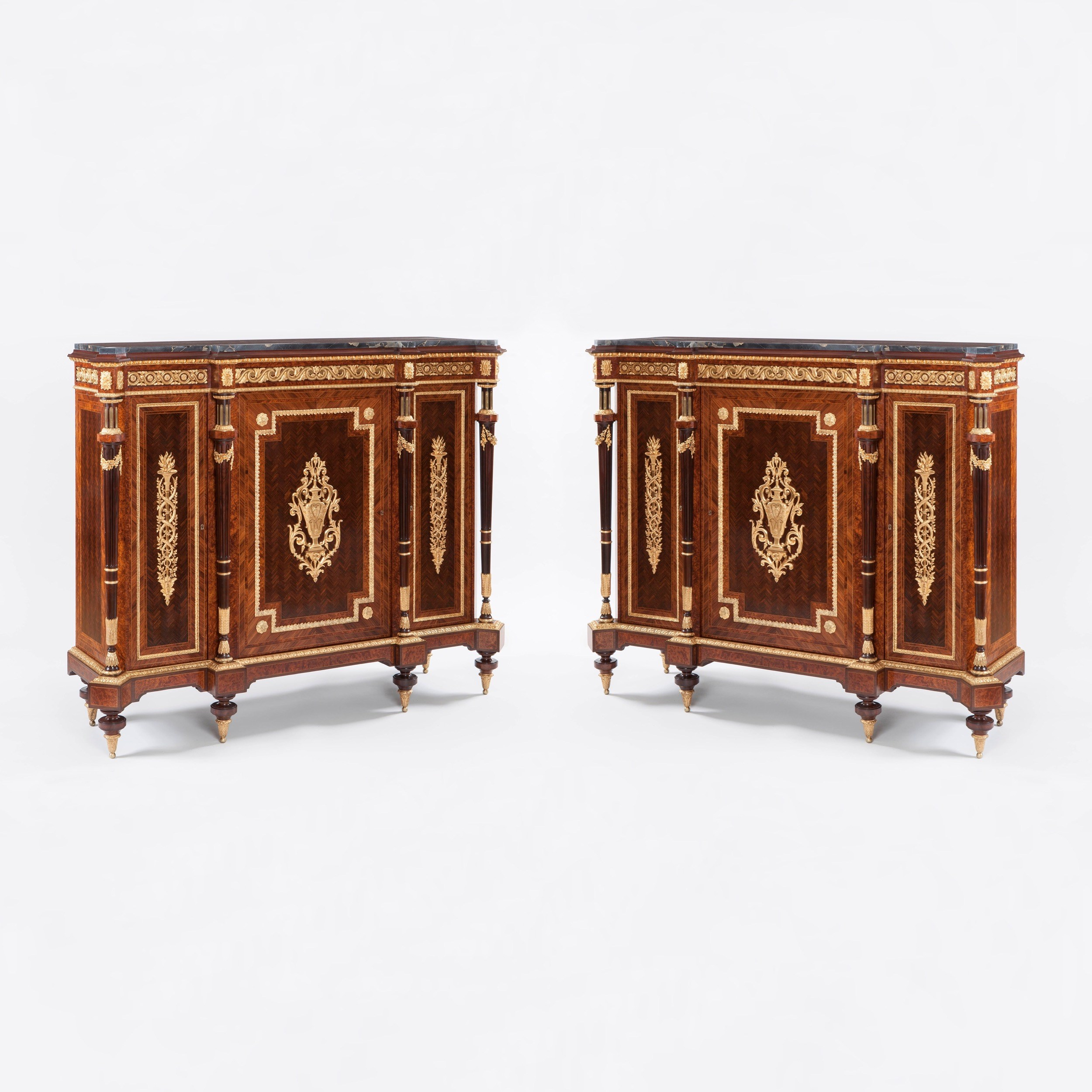 A Good Pair of Meuble d'Hauteurs d'Appui By Henri Picard of the Napoleon III Period Constructed using fine kingwood, thuyawood and amaranth veneers laid in complex book matched and chevron parquetry, and dressed with excellent gilt bronze mounts stamped on the reverse 'HPR' for Henry Picard of Paris; of breakfront form with everted angles, each rising from six tapering ormolu toupie feet supporting shaped, and ormolu dressed plinths, with three lockable doors enclosing shelved interiors, interspersed with ormolu swag and stiff leaf decorated fluted, ring-turned and tapering columns; the central doors with ormolu stylised Grecian urns within leaf cast ormolu frames set with paterae at the inverted angles: the flanking doors dressed with ormolu interwoven branches issuing flambeaux; the sides with further conforming parquetry and ormolu mounts, with the upper aprons set with Vitruvian form ormolu friezes, and having Portor marble inset platforms with everted angles. Bearing an old paper label reading 'Roux No.49, 1 Bahal'. French, Circa 1870 Dimensions: H: 52 in / 131.5 cm  |  W: 65 in / 164 cm  |  D: 19.5 in / 49 cm Similar models are recorded in Christopher Payne's '19th Century European Furniture' published by the Antique Collectors Club in 1981 Henri Picard, a notable fondeur and doreur, is recorded as working in Paris from 1831 to 1864, from 6 rue Jarente and later at 10 rue de la Perle. Their work was highly regarded by the Emperor Napoleon the Third, and they supplied furniture to his apartments in Fontainebleu, now on exhibit in the Louvre.