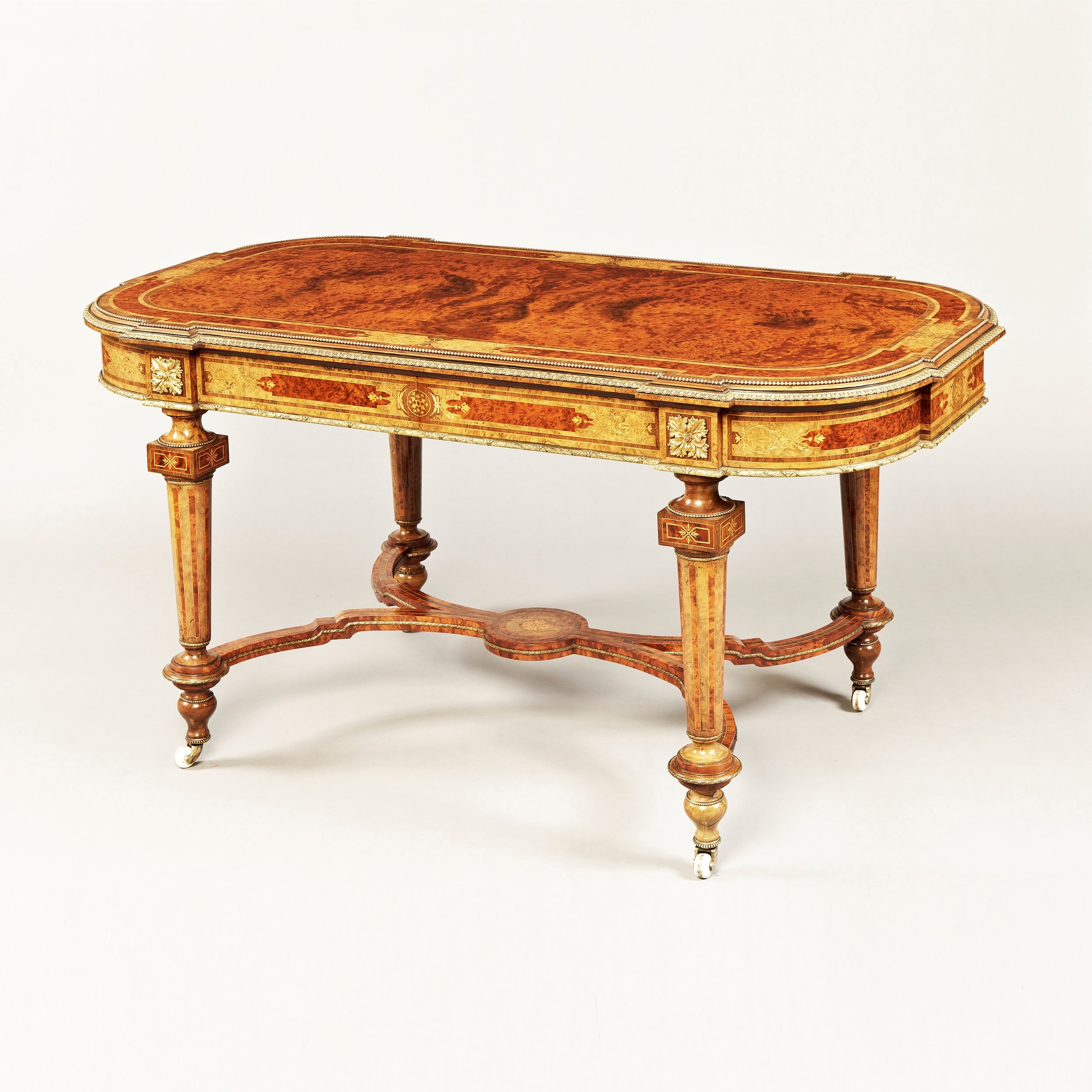 A Very Fine and Substantial Centre Table In the Louis XVIth Manner of Holland & Sons  Of exceptional quality, utilising beautifully grained woods, including Circassian walnut, thuya, purple heart and boxwood in the construction, and adorned with very finely cast, planished and gilded ormolu mounts; rising on four tapering turned and inlaid porcelain castor shod legs, conjoined by a shaped and stepped 'X' form stretcher, with a central vase stand, inlaid with a circular patera; the symmetrical shaped serpentine cross banded and inlaid top, richly dressed with ormolu running pearl banding and to the edges, a stylised ormolu gadroon; the apron housing two drawers, lined with quadrant mouldings  Circa 1850  Dimensions: H: 30 in / 76.5 cm   W: 60 in / 152.5 cm   D: 32 in / 81.5 cm  Provenance; Whitbourne Hall, Worcester  Family tradition believes the table was supplied by the London decorators, Cowtan & Company, who were absorbed into Colefax & Fowler in the 1970s.  Please see Symonds & Whineray, Victorian Furniture pages 169 and 187 illustrations of similar items of furniture  Ref 7874